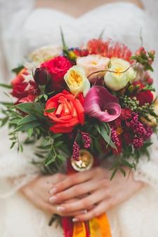 La sposa in un bellissimo abito bianco da sposa in possesso di un bouquet.