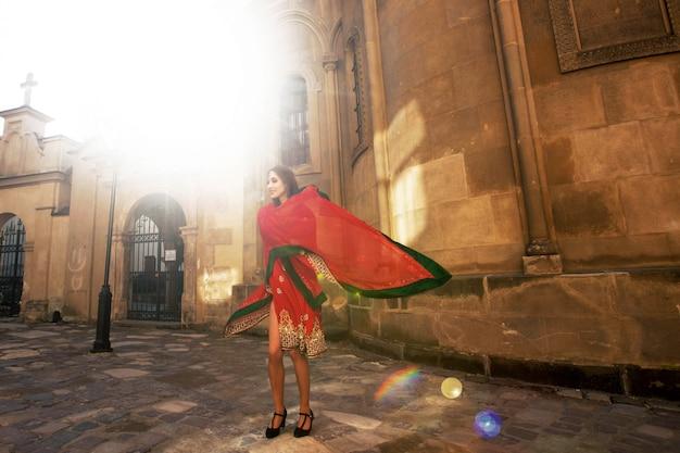 La sposa indiana solleva il suo rosso sari in posa nei raggi di luce del mattino