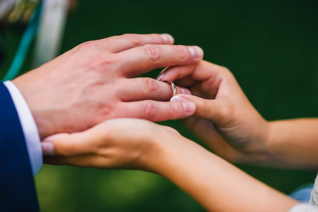 La sposa indossa l'anello sul dito dello sposo alla cerimonia di nozze