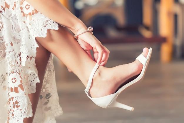 La sposa indossa scarpe da sposa ai suoi piedi