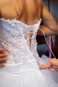 La sposa indossa un abito prima della cerimonia nuziale.
