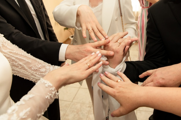 La sposa, lo sposo e il gruppo di ospiti di nozze mostra gli anelli di nozze