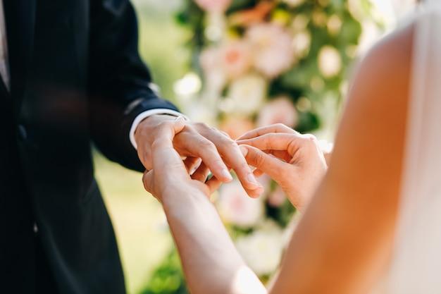 La sposa mette l'anello di nozze sul dito dello sposo. senza faccia