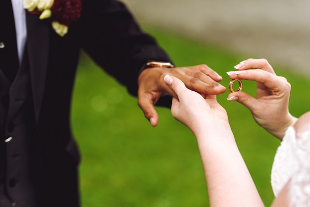 La sposa mette l'anello di nozze sul dito dello sposo