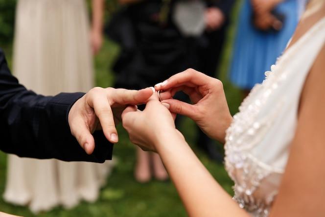 La sposa mette la fede nuziale sul dito dello sposo durante la cerimonia nel parco