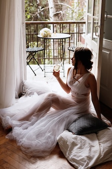 La sposa nel penioire si siede sul balcone con un bicchiere di champagne