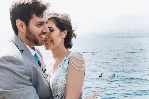La sposa si appoggia a toelettatura tenera in piedi davanti al mare