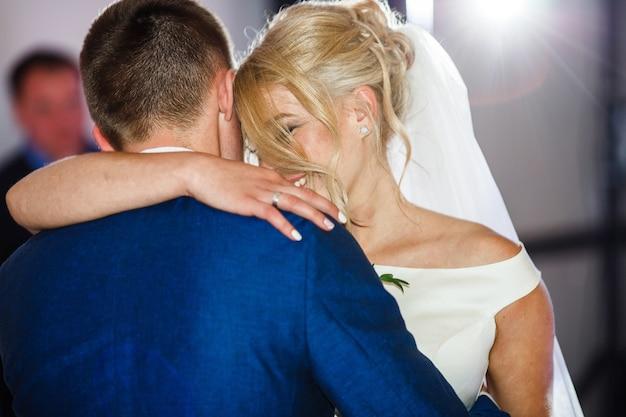 La sposa si appoggia a uno sposo tenero che balla con lui