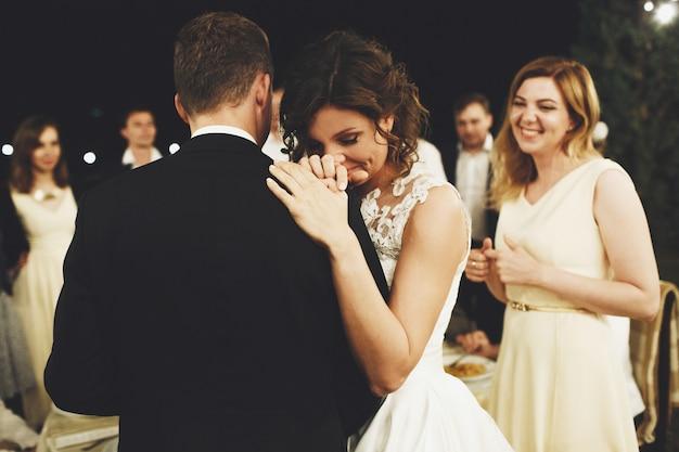 La sposa si appoggia alla spalla dello sposo in piedi con gli amici nel cortile di casa la sera