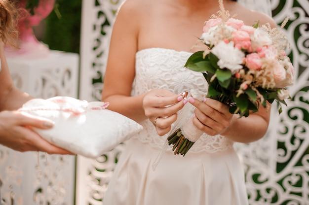 La sposa si è vestita in un bello vestito da sposa bianco che tiene un anello