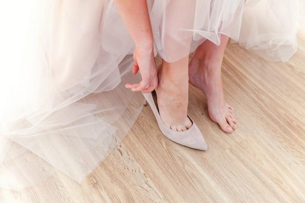 La sposa si prepara per la cerimonia indossando belle scarpe a piedi nel giorno del matrimonio