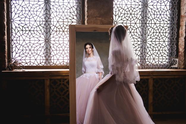 La sposa si raduna al mattino vicino allo specchio