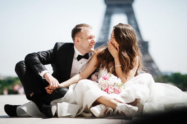 La sposa si siede nelle risatine prima della torre eiffel a parigi mentre lo sposo tiene la sua mano