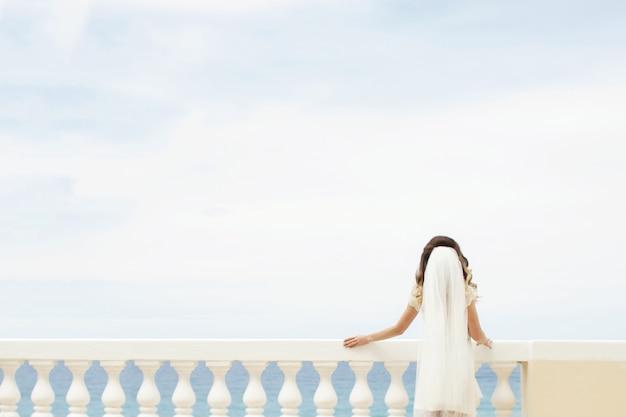 La sposa si sporge su un balcone bianco mentre ammira il mare