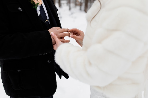 La sposa sta mettendo un anello al dito dello sposo all'aperto