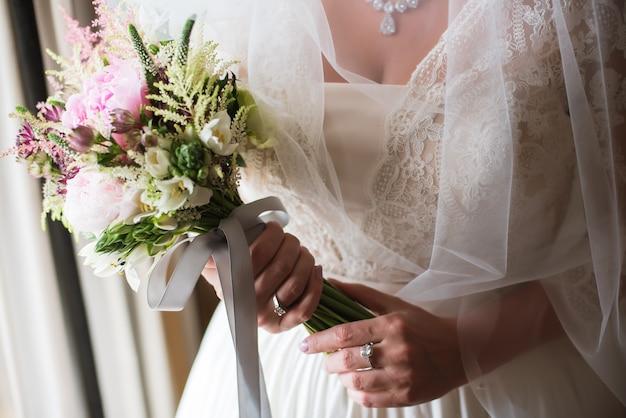 La sposa sta tenendo il mazzo di nozze in mani
