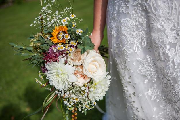 La sposa sta tenendo un mazzo di fiori freschi dell'estate e della primavera nei colori pastelli su un fondo vago, fuoco selettivo
