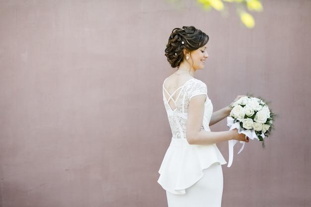 La sposa sta vicino a un muro dell'edificio, tiene un bouquet da sposa e sorride