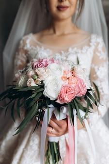 La sposa tiene il bellissimo bouquet da sposa con rose bianche e rosa
