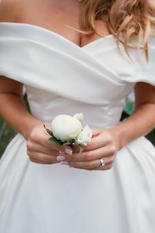 La sposa tiene in braccio un piccolo fiore all'occhiello bianco