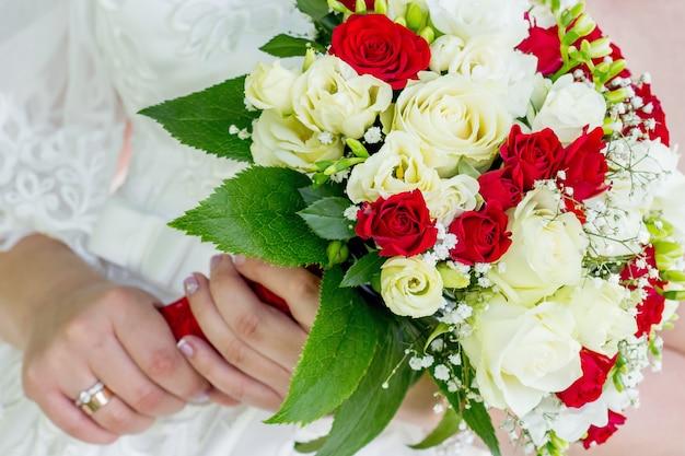 La sposa tiene in mano un elegante bouquet da sposa