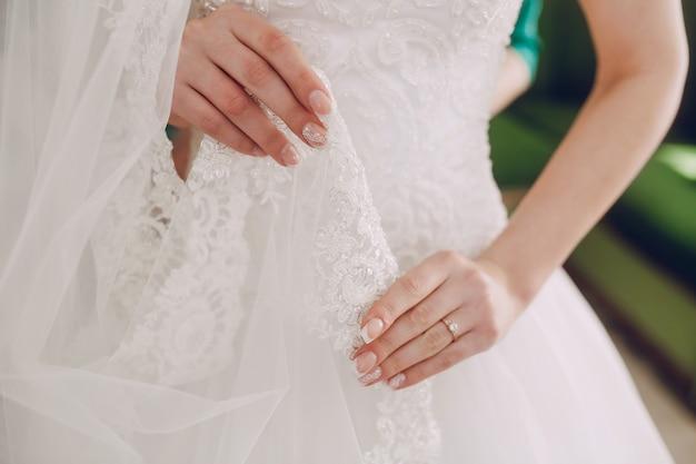 La sposa toccando il suo abito da sposa