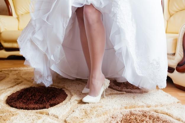La sposa veste le scarpe prima della cerimonia nuziale
