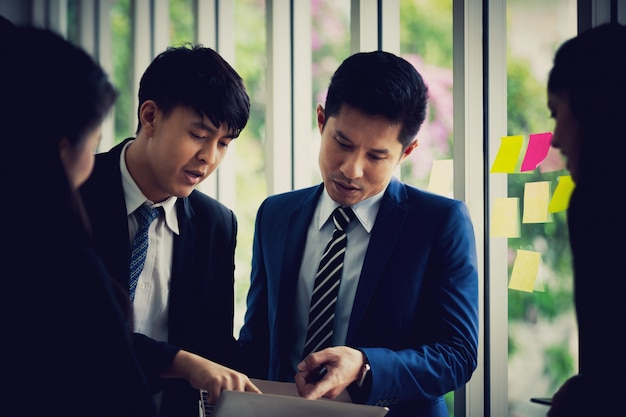 La squadra di affari asiatica che sta parlante lavora nella stanza dell'ufficio