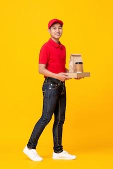 La squadra maschio del fast food in uniforme rossa che consegna porta via il pasto