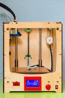 La stampante 3d ha completato la creazione di un modello in miniatura di uno scooter in plastica. la stampante 3d è al chiuso, primo piano
