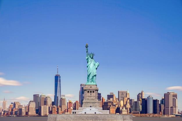 La statua della libertà con il one world trade center edificio sul fiume hudson e lo sfondo del paesaggio urbano di new york, punti di riferimento di manhattan new york city.