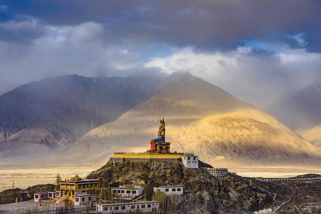 La statua di maitreya buddha con le montagne dell'himalaya sullo sfondo dal monastero di diskit, in india.