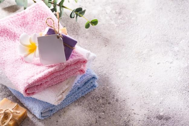 La stazione termale ha messo dagli asciugamani di bagno naturali freschi con sapone e fiore fatti a mano su un fondo grigio chiaro.