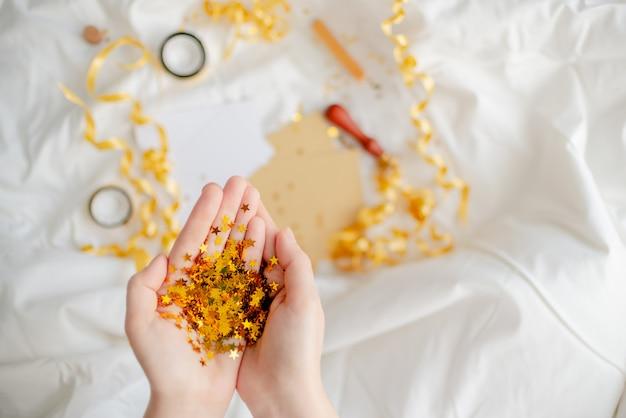La stella luminosa festiva dei coriandoli dorati scintilla mano della donna. vista superiore della festa di compleanno concettuale creativa di natale