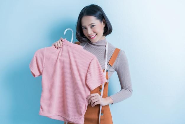 La stilista asiatica sta mostrando la maglietta che sta disegnando.