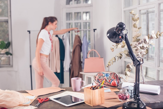 La stilista femmina che lavora in studio seduto sulla scrivania