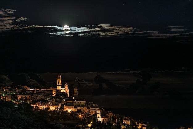 La storica città di cervo incandescente nella notte al chiaro di luna e cielo stellato sulla costa della riviera ligure, italia.
