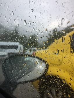 La strada con le auto è fotografata attraverso il parabrezza della macchina, schizzato dalla pioggia.