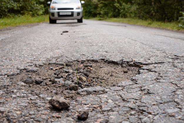 La strada deve essere riparata. strada di campagna con grande buca