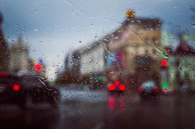 La strada di città vista attraverso le gocce di pioggia sul parabrezza dell'automobile
