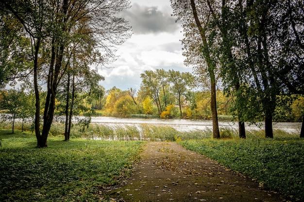 La strada nel parco che porta al fiume in autunno. paesaggio autunnale con fiume e alberi