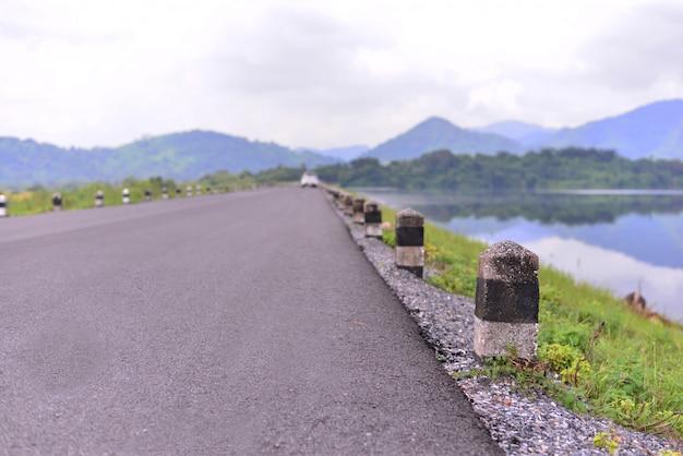 La strada, palo di colonna in cemento bianco e nero accanto alla strada