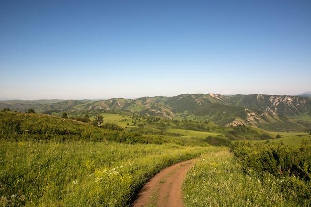 La strada sterrata conduce alle montagne.
