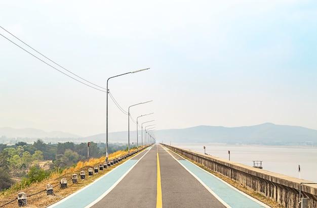 La strada sulla diga montagne di sfondo e acqua alla diga di krasiew