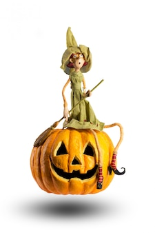 La strega di halloween si siede sulla zucca intagliata