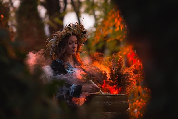 La strega fa l'incantesimo con il calderone sulla foresta