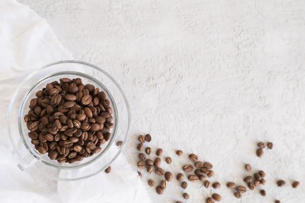 La struttura dell'aroma fot testo fatto dei chicchi di caffè di vetro della tazza su fondo grigio