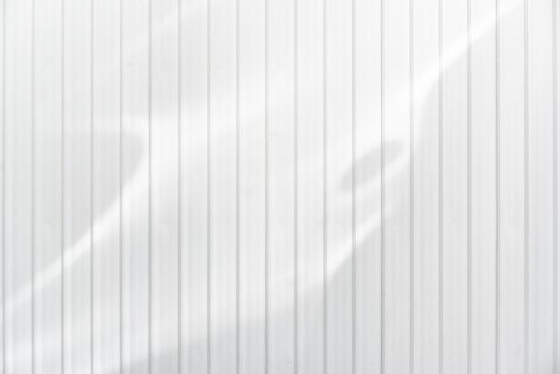 La struttura ondulata bianca della parete del metallo con estratto ha riflesso la luce solare. trama di sfondo orizzontale.