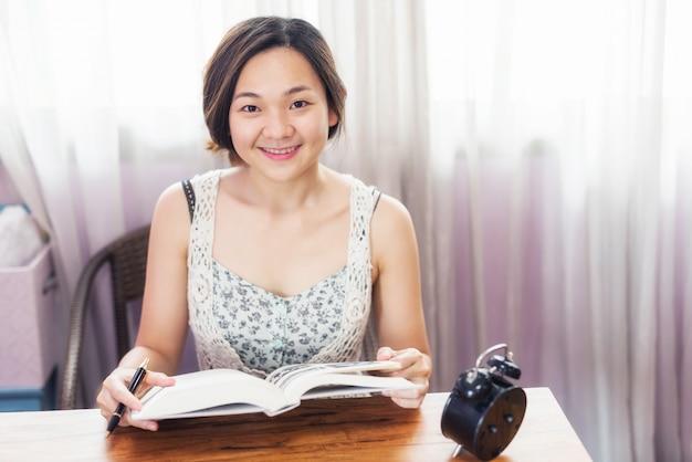 La studentessa asiatica ha letto il libro per esame finale