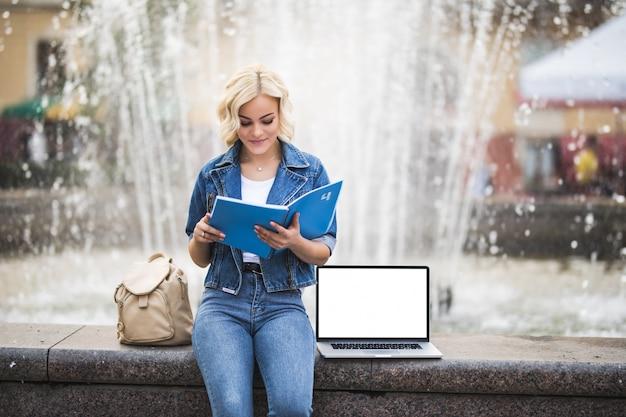 La studentessa bella ragazza bionda lavora sul suo computer portatile e legge il libro vicino alla fontana della città nel corso della giornata